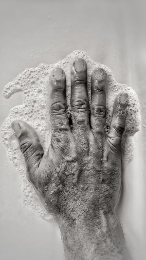 Close-up of hand on sand