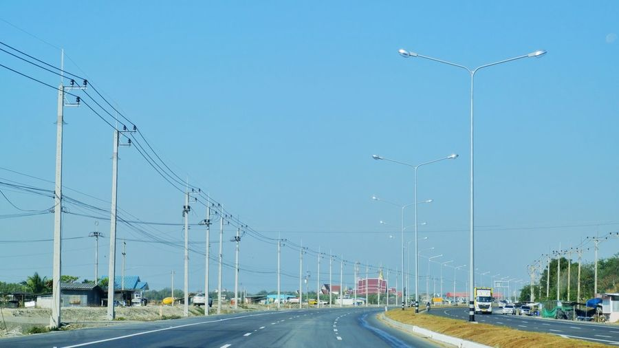 Vehicles on road against clear sky