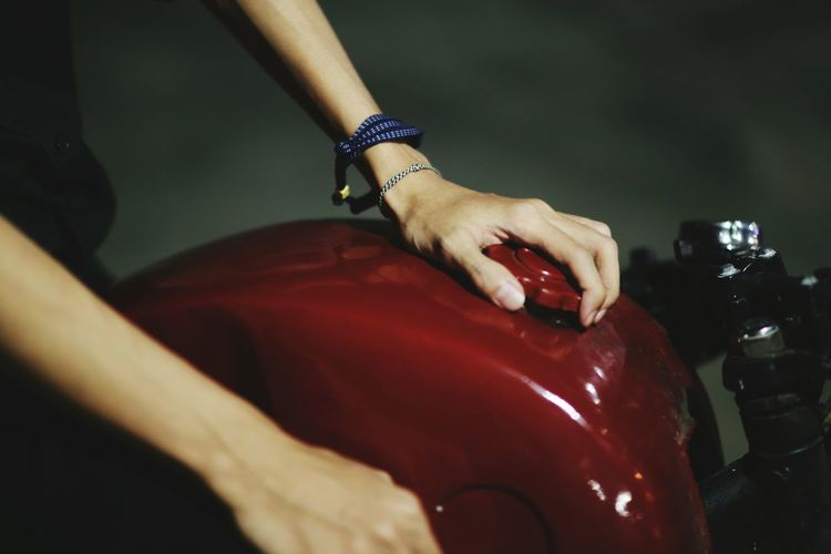 Cropped hands of person holding motorcycle