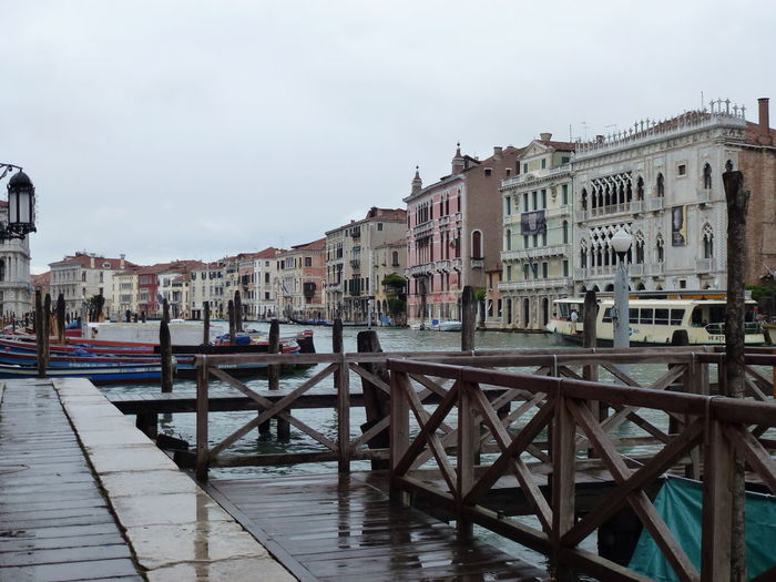 Pier at grand canal by buildings against sky