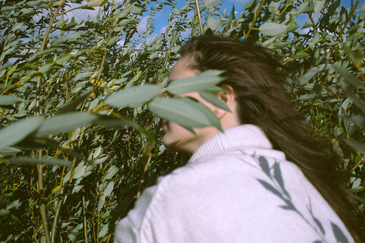 Portrait of young woman lying on plant