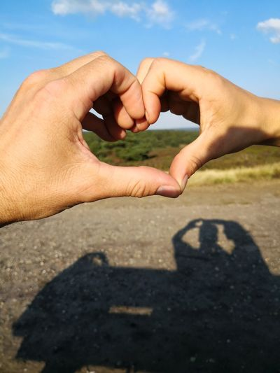 Close-up of hands forming heart shape against sky