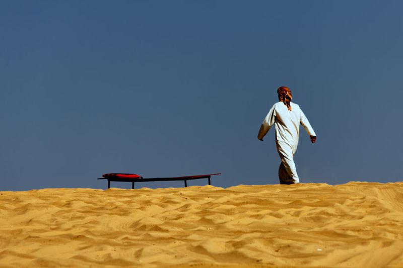 Man walking at desert against clear sky