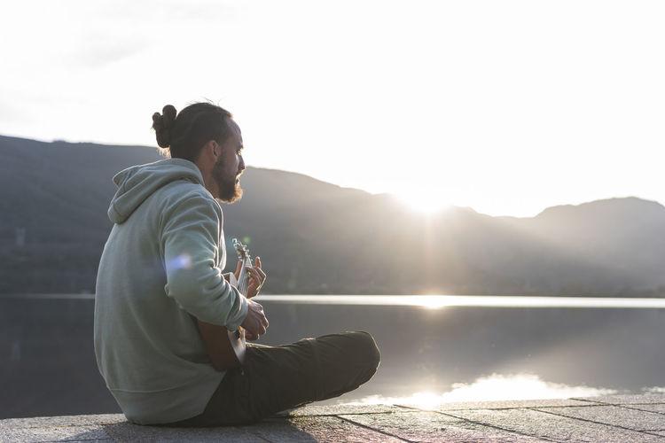 Man sitting by lake against mountain