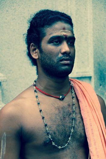 Shirtless sadhu looking away