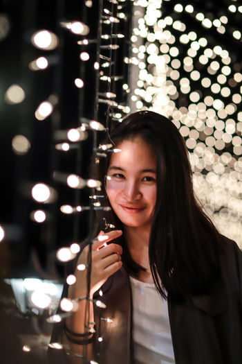 Portrait of smiling young woman by illuminated string lights at night