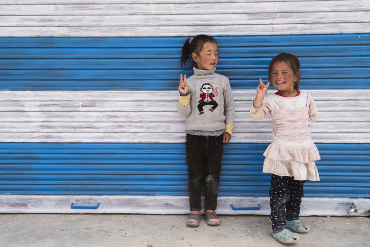 Portrait of children standing against wall