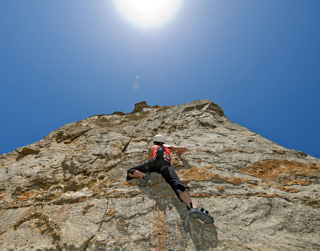 Man climbing rock on mountain against sky