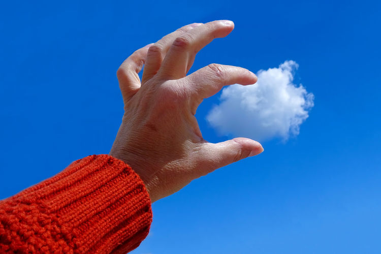Low angle view of human hand against blue sky