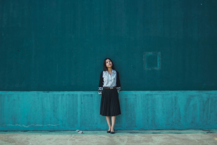 Full length of young woman standing against blue wall