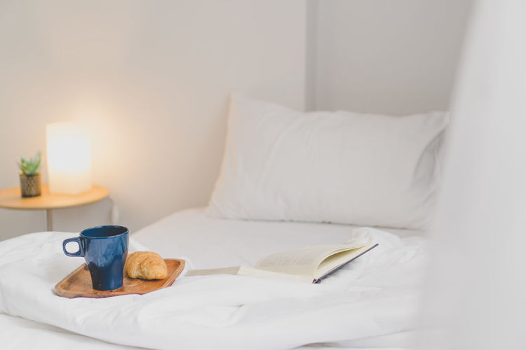 Book and crockery on bed at illuminated home