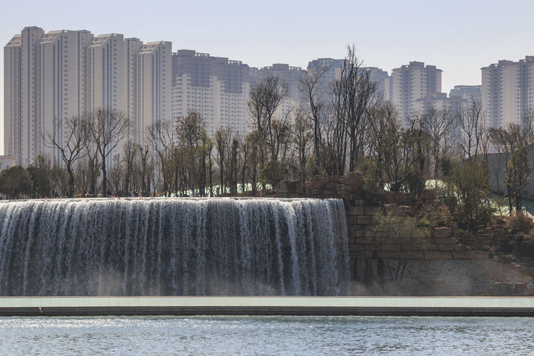 Kunming, China - March 4, 2016: Kunming Waterfall park featuring a 400 meter wide manmade waterfall. Kunming is Yunnan's capital Architecture ASIA Asian  Building Built Structure City Dalí Dianchi Lake Indochina Landmark Lijiang Modern Niulan River Office Building Park River Shangrila Sky Skyscraper Tourists Tree Water Waterfall Park Xinhua, Yunnan