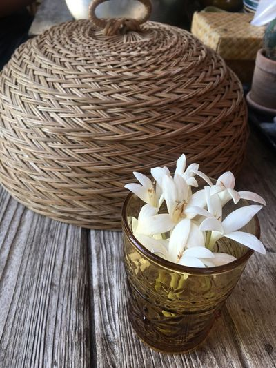 Close-up of white flowers in basket on table