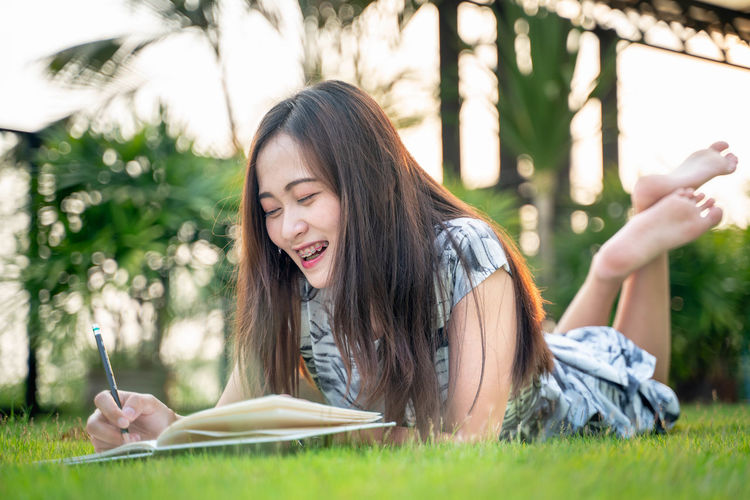 One Person Young Adult Publication Leisure Activity Book Grass Young Women Plant Lying Down Holding Lifestyles Real People Day Education Reading Nature Casual Clothing Relaxation Hairstyle Studying Outdoors Note Pad