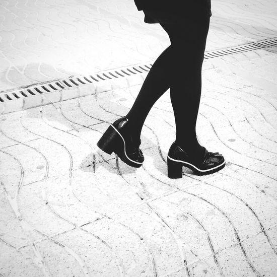 Low section of woman wearing high heels walking on street