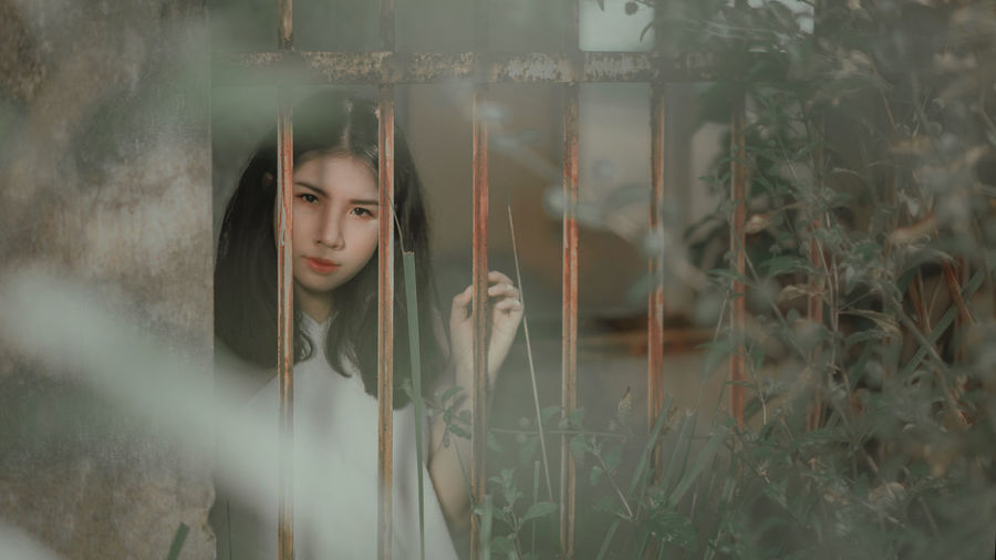 Young woman standing in cage