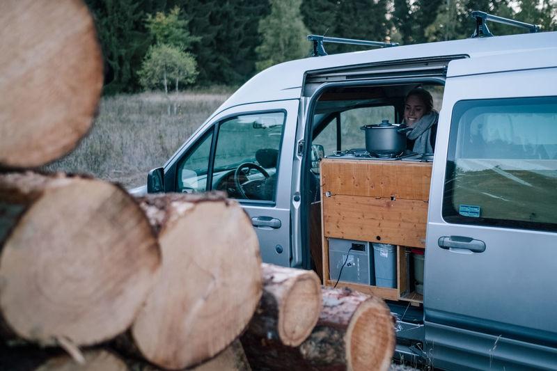 Woman in car by logs