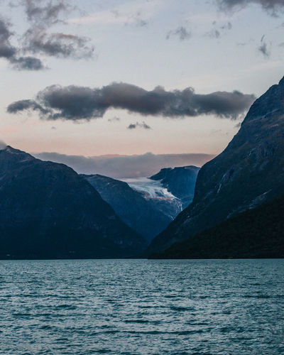 Layered mountain range over a fjord water and dusk sky