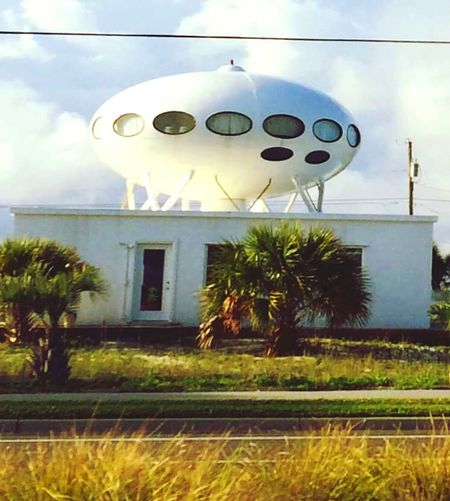 """Spaceship House Picture Blurry on Pensacola Beach Santa Rosa Island Florida United States Architecture Spaceship Houseis the name commonly given to the structure at1304 Panferio DriveinPensacola Beach. The house, which resembles popular depictions of alienUFOs, is actually a """"Futuro"""" prefabricated house. Designed in the 1960s by Finnish architect Matti Suuronen, about a hundred were constructed. The Pensacola Beach Futuro was built in 1966 and sits atop a lower structure made of concrete block. A fifty-foot walkway leads up to the Futuro and a surrounding patio"""