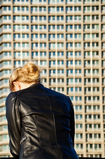 Rear view of woman wearing leather jacket while standing against building