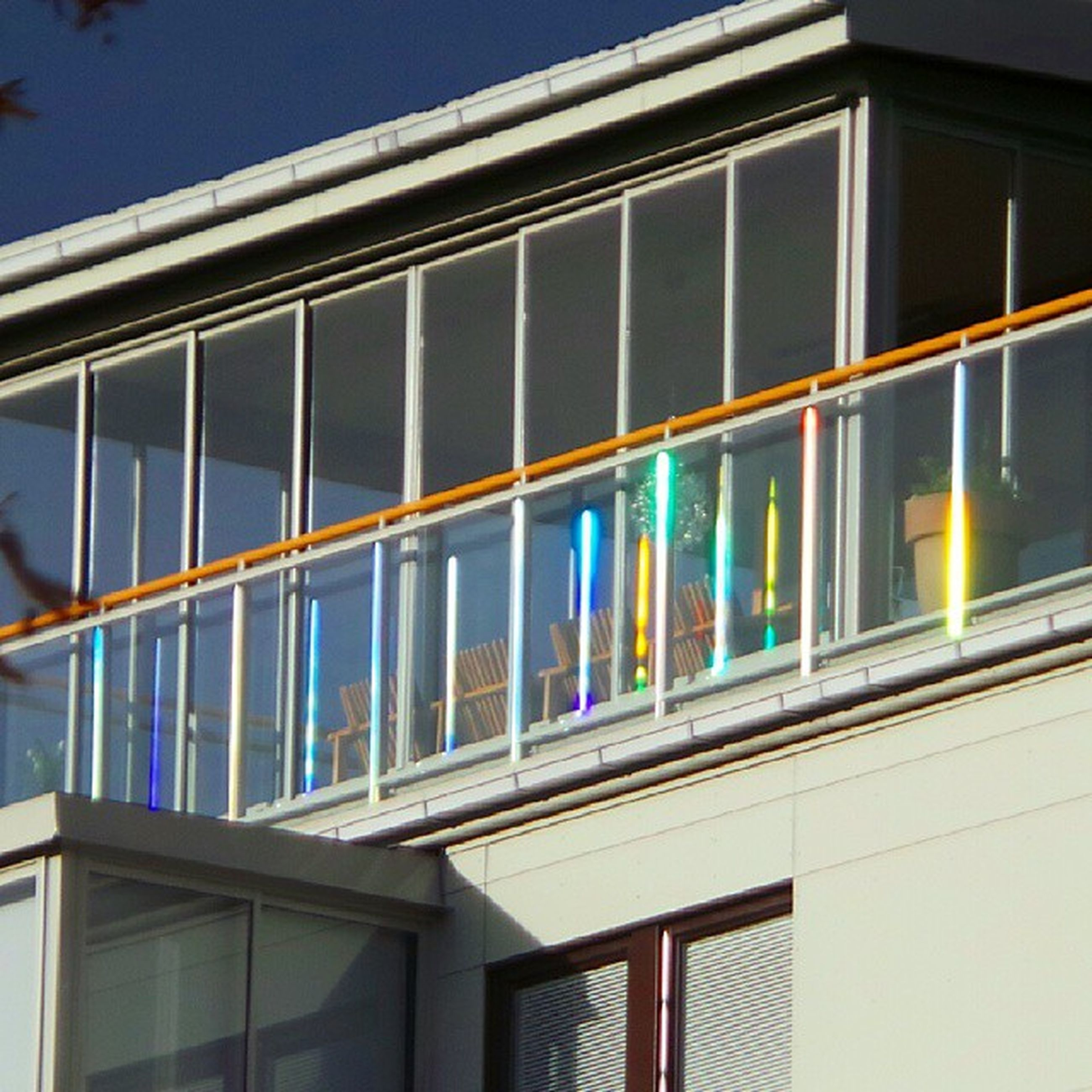 architecture, built structure, building exterior, window, low angle view, glass - material, building, blue, reflection, city, railing, balcony, clear sky, modern, sky, city life, outdoors, day, transparent, illuminated