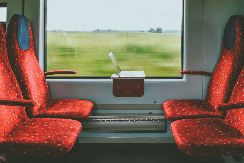 Workplace in the train Chair Computer Day Glass - Material Indoors  Laptop Motion Blur No People PC Red Remote Work Seat Transportation Traveling Tree Vehicle Interior Vehicle Seat Window Working In Train Working Place Let's Go. Together.