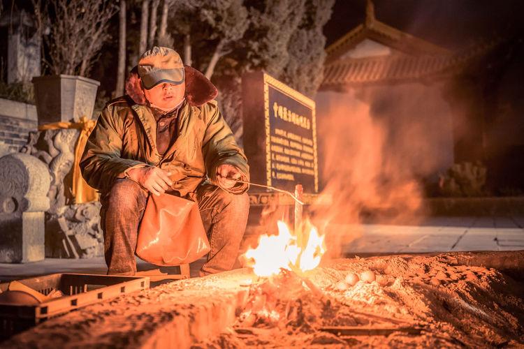 Man Sitting By Bonfire At Night