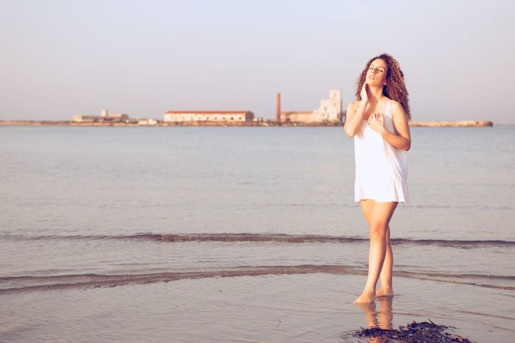 Young woman standing on beach against clear sky