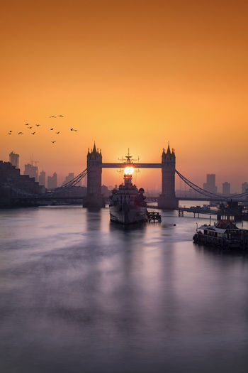 Idyllic sunrise behind the Tower Bridge in London, UK Waterfront Water Building Exterior Architecture Sunset Sky River City Orange Color Travel Destinations Bridge No People Cityscape Travel Tourism Outdoors London United Kingdom Tower Bridge  Sunrise Thames Long Exposure Tourist Attraction  Sun Landmark