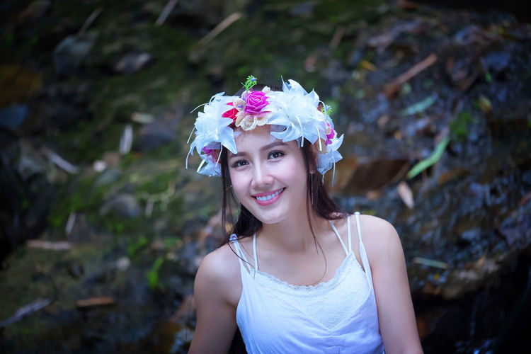 Close-Up Portrait Of Smiling Young Woman Wearing Wreath In Forest