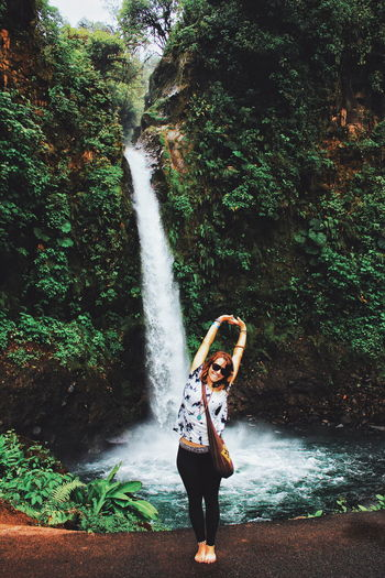 Happy woman standing with arms raised against waterfall in rainforest