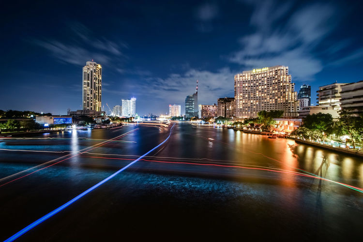 High angle view of light trails on chao phraya river in city at night