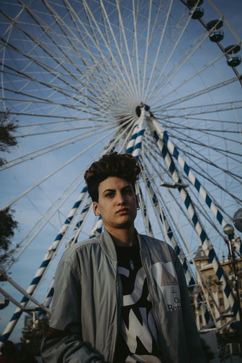 Portrait Young Men Leisure Activity Young Adult One Person Front View Looking At Camera Ferris Wheel Amusement Park Amusement Park Ride Real People Casual Clothing Waist Up Sky Day Lifestyles Arts Culture And Entertainment Outdoors Teenager Contemplation