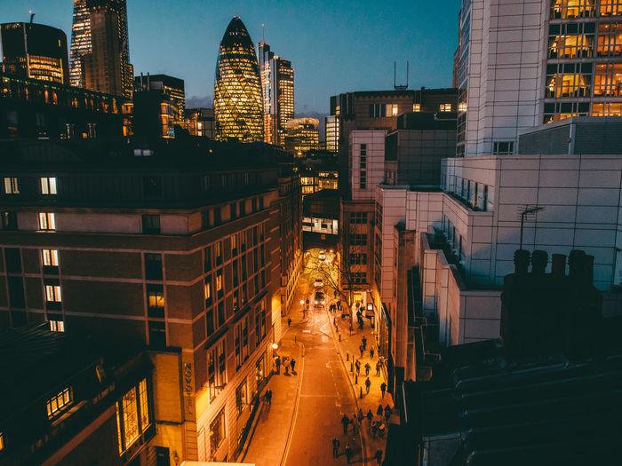 Illuminated city street amidst buildings by 30 st mary axe at dusk
