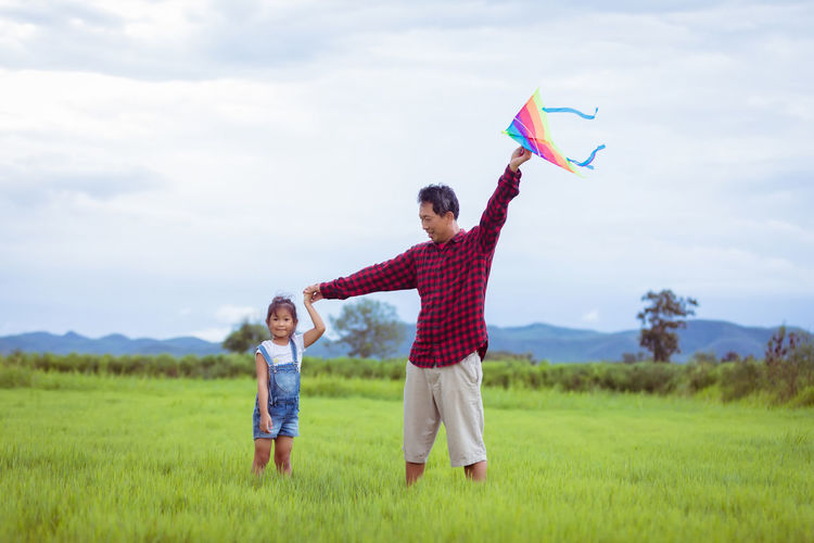 Man holding kite while standing with daughter on grassy field