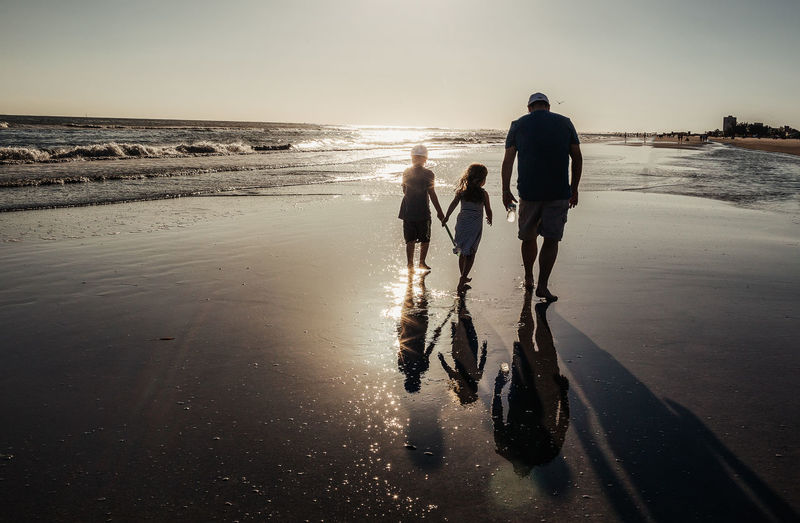 Beach Water Land Sea Togetherness Full Length Family Child Real People Sky Love Childhood Reflection Bonding Nature Positive Emotion Walking Horizon Over Water Daughter Son Father Vacation