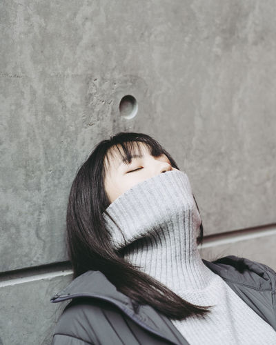 Close-up of young woman covering mouth with turtleneck against wall