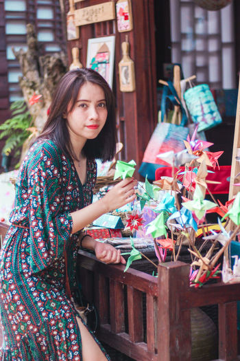 Portrait of woman holding origami at store