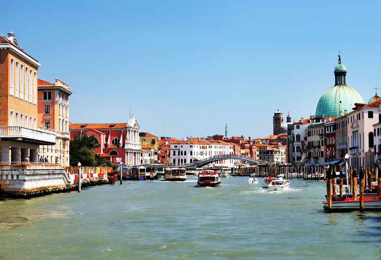 Boats moving on grand canal amidst buildings against clear blue sky