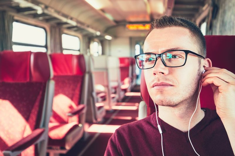 Young Man Listening To Music While Traveling In Bus