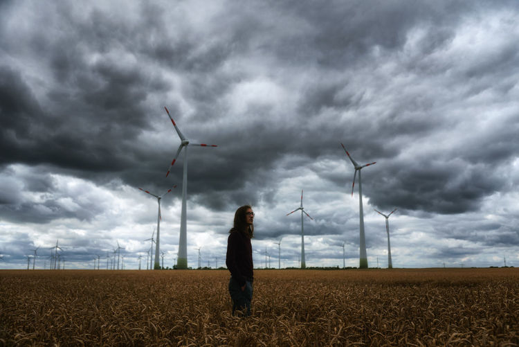 Man standing on field by windmills against cloudy sky