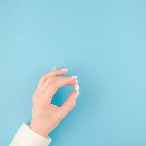Close-up of person hand holding pill against blue background