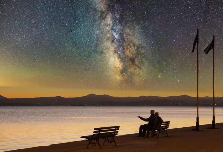 Silhouette man sitting on seat in lake against sky at night
