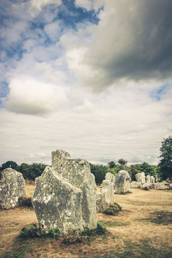 Rocks on field against cloudy sky