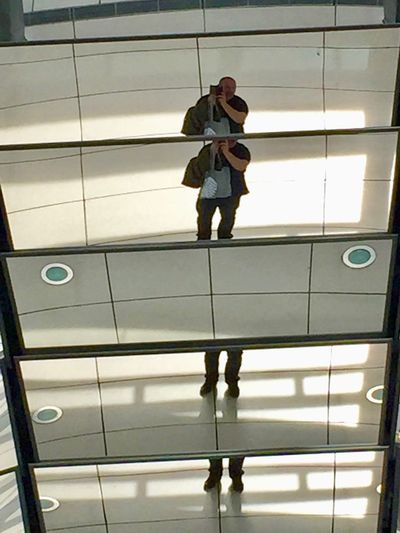 Low angle view of man and woman walking on glass