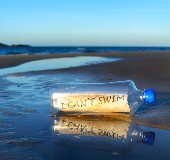 Bottle with message at beach against blue sky