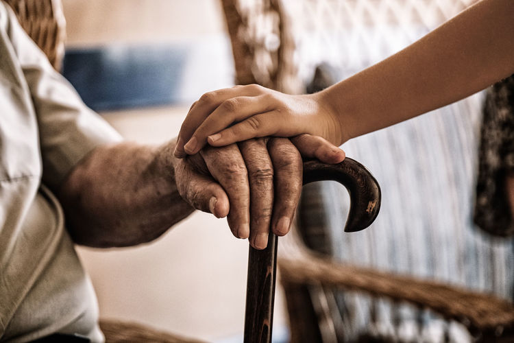 Midsection of man touching grandfather hand