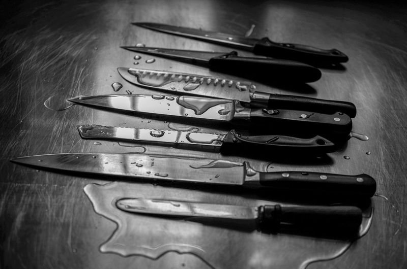 High angle view of wet knives on table