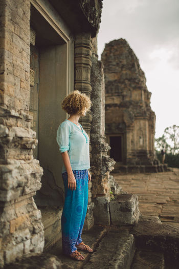 Side View Of Mid Adult Woman Standing At Angkor Wat Entrance