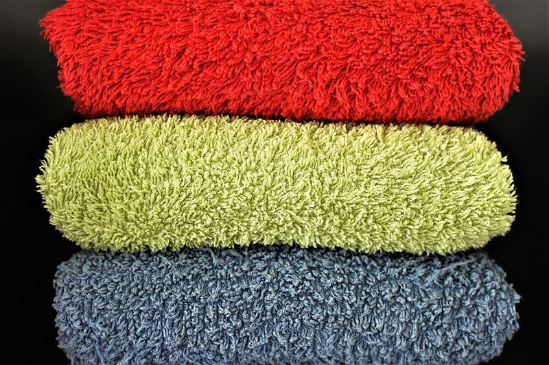 Close-Up Of Colorful Folded Rugs Against Black Background